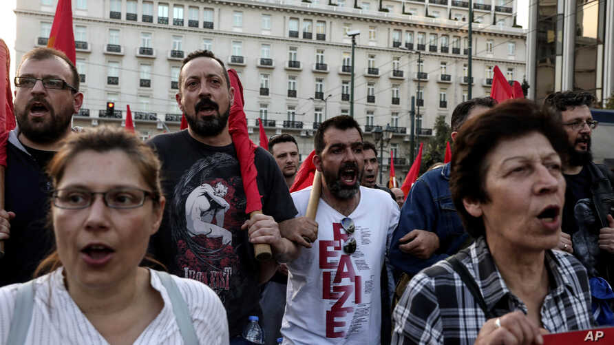 Supporters of the Greek Communist party chant slogans during an anti-war rally in front of the parliament, in Athens, Saturday, April 14, 2018.