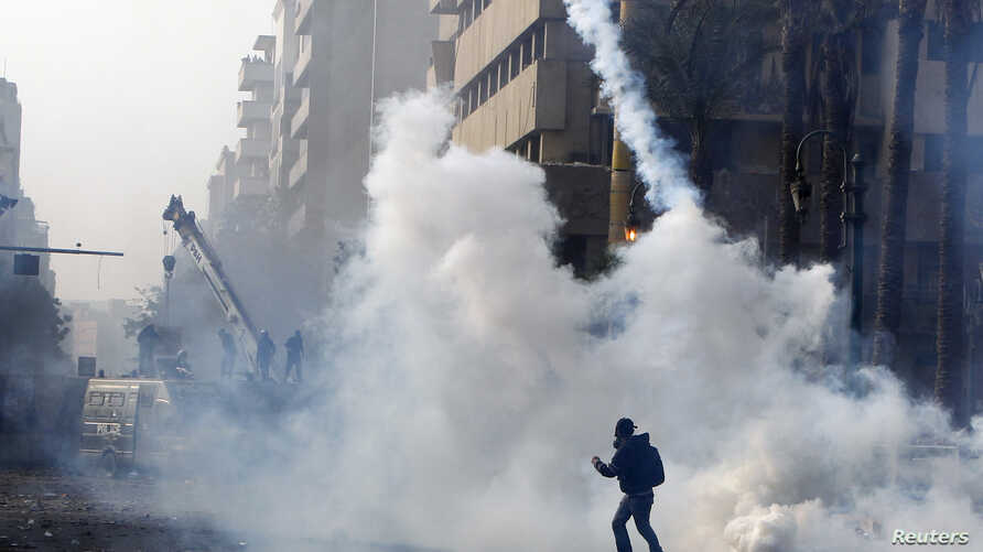 A protester throws a tear gas canister back at riot police in Cairo November 25, 2012.