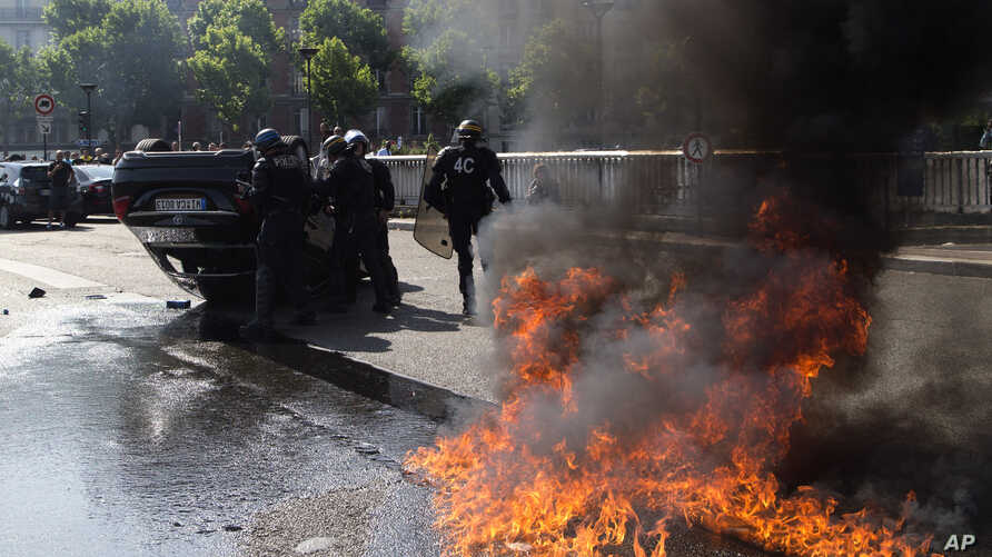 Riot police stand by an overthrown car during a demonstration by taxi drivers opposed to ride-sharing service Uber in Paris, June 25, 2015.