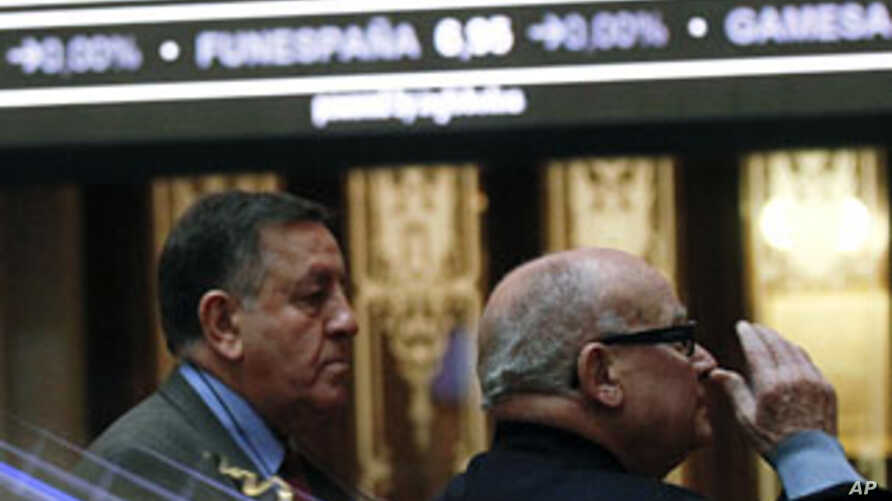 Traders look at a stock index board at Madrid's stock exchange, January 16, 2012