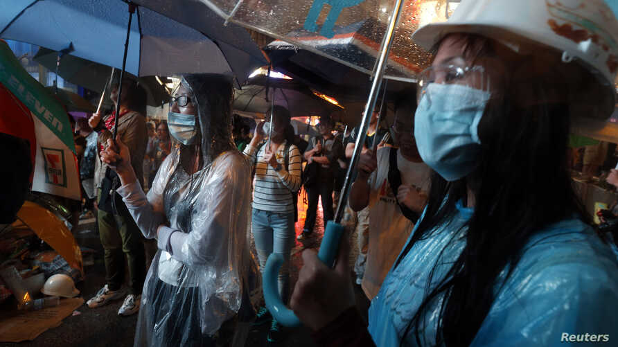Pro-democracy protesters stand in heavy rain while blocking a main road at Mongkok shopping district in Hong Kong, October 22, 2014.
