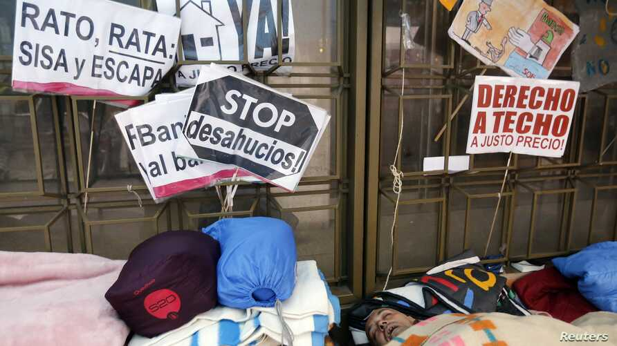 People sleep outside the headquarters of Spanish nationalized lender Bankia, where protesters have camped for more than three weeks, in Madrid, November 20, 2012.