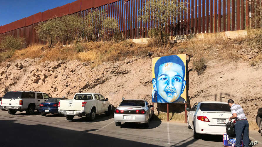 FILE - This is the boundary between the U.S. and Mexico at Nogales, Mexico, Dec. 4, 2017. The poster is of Juan Antonio Elena Rodriguez, a teen who was shot and killed by a Border Patrol agent who shot through the fence in 2010.