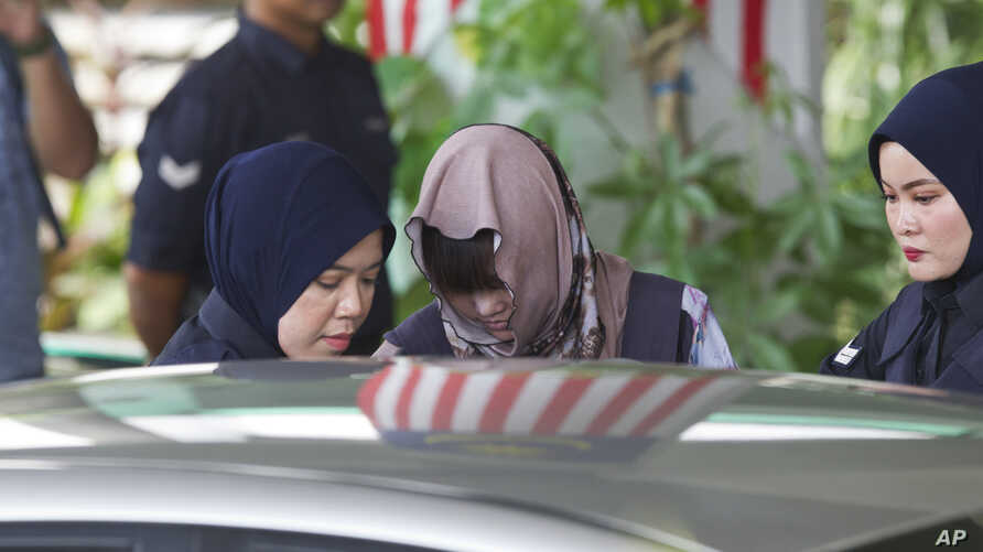 FILE - Vietnamese Doan Thi Huong (C) is escorted by police as she leaves the Shah Alam High Court after a hearing in Shah Alam, Malaysia, Nov. 7, 2018.