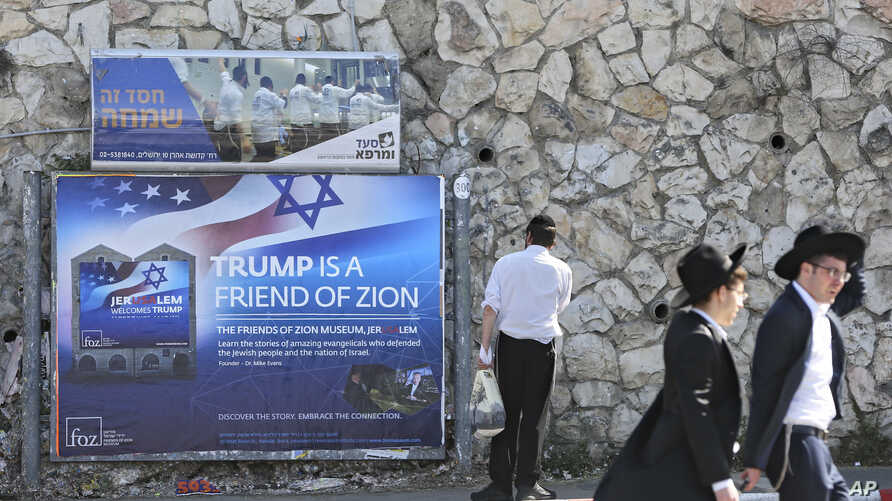 Ultra-Orthodox Jews pass by a billboard welcoming President Donald Trump ahed of his visit, in Jerusalem, May 19, 2017.