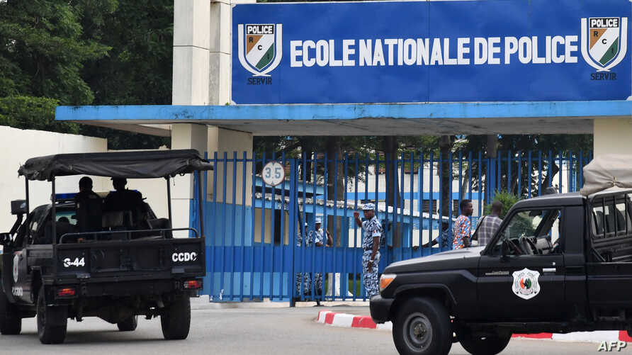 A picture taken on July 20, 2017 shows two vehicles of the Ivorian police's special forces (CCDO) outside the entrance to the National Police Academy in the district of Cocody in Abidjan, where gunshots were reportedly fired on July 19.