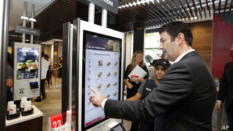 FILE - In this Thursday, Nov. 17, 2016, file photo, McDonald's CEO Steve Easterbrook demonstrates an order kiosk, with cashier Esmirna DeLeon, during a presentation at a McDonald's restaurant in New York's Tribeca neighborhood.