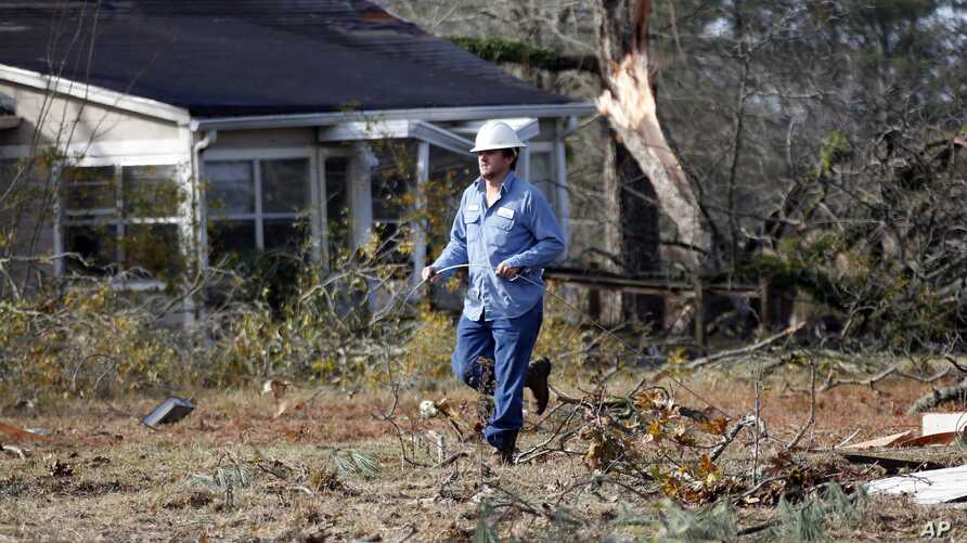 A Central Electric Power Association lineman pulls a new line across the debris littered lawn of a Scott County, Mississippi, resident, Wednesday, Nov. 30, 2016, that was damaged by an apparent tornado Tuesday afternoon. With crowd-sourced mapping re