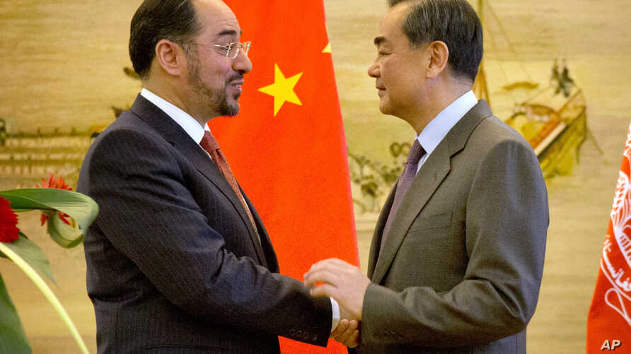 Afghan Foreign Minister Salahuddin Rabbani, left, and Chinese Foreign Minister Wang Yi, right, shake hands at the end of a joint press conference at the Ministry of Foreign Affairs in Beijing, Jan. 26, 2016.