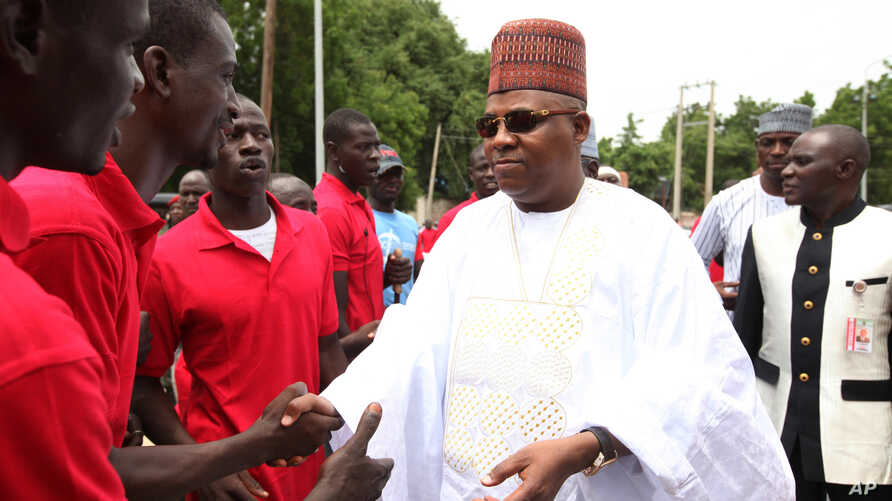 """FILE- In this Thursday, Aug. 8, 2013 file photo, Borno state governor Kashim Shettima, right, shake hands with members of the """"Civilian JTF"""",  in Maiduguri Nigeria.  The governor of Nigeria's northeast Borno state Shettima has temporarily relocated t"""