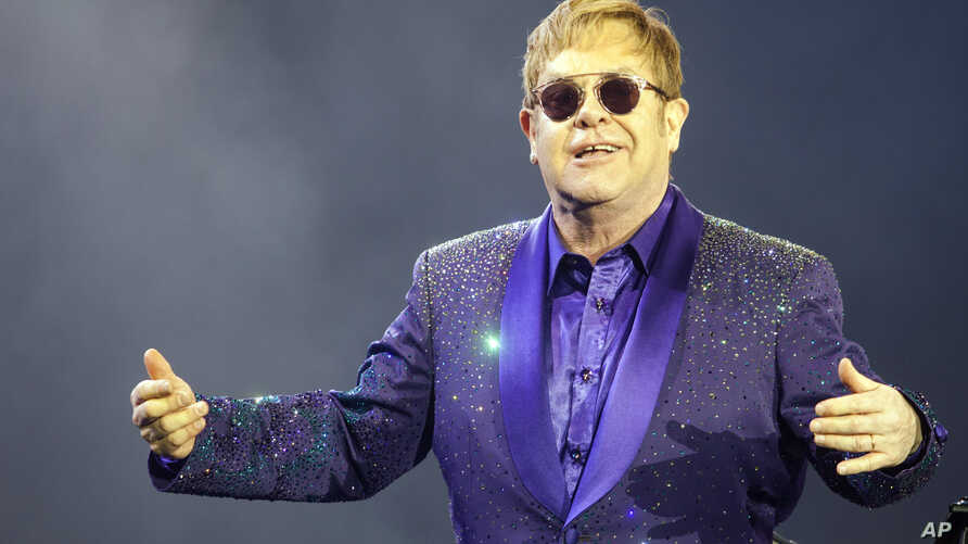 FILE- Musician Elton John performs during a show in Tel Aviv, May 26, 2016.