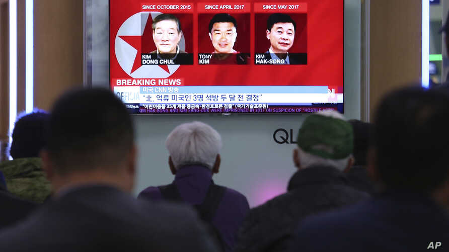 People watch a TV news report screen showing portraits of three Americans, Kim Dong Chul, left, Tony Kim and Kim Hak Song, right, detained in the North Korea at the Seoul Railway Station in Seoul, South Korea, May 3, 2018.