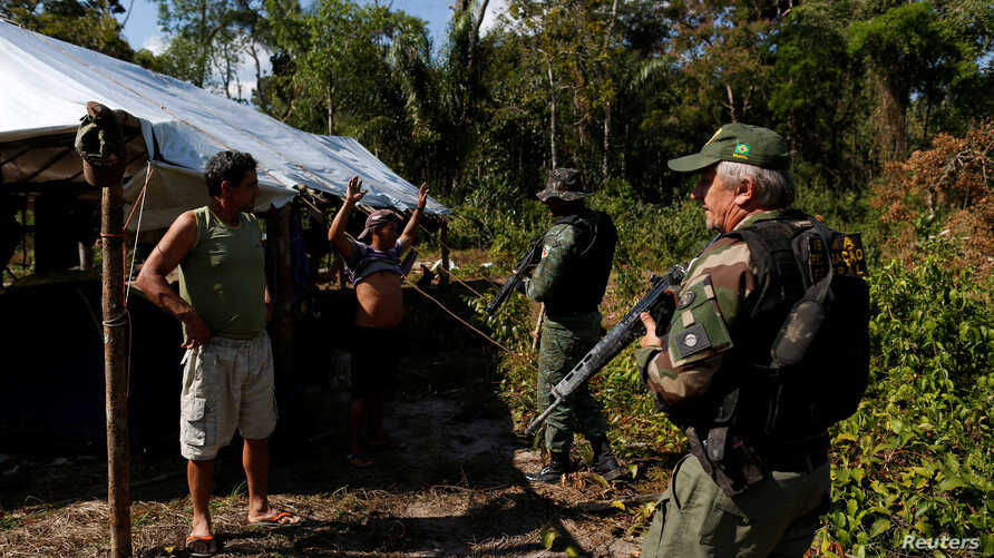 """FILE - Agents of the Brazilian Institute for the Environment and Renewable Natural Resources check a man at in illegal logging camp during """"Operation Green Wave,"""" Aug. 21, 2017. Trusting that every effort will help to save rainforest, Environment Min"""