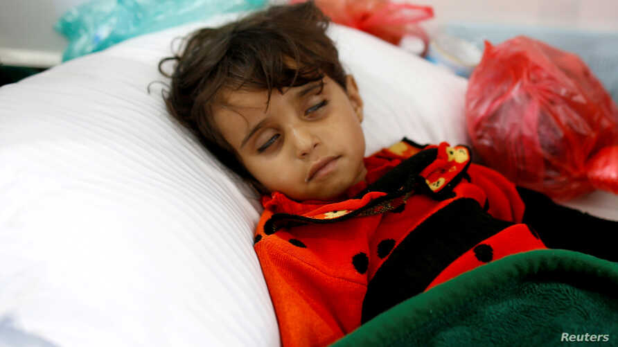 FILE - A girl infected with cholera lies on the ground at a hospital in Sana'a, Yemen, May 7, 2017.