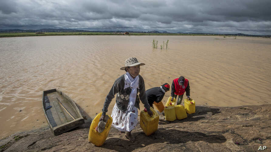 Residents cross flooded land and canal in Madagascar's capital Antananarivo, to collect fresh water, March 10, 2017.