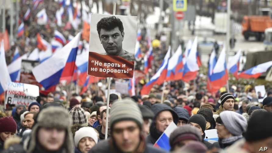 """Demonstrators, with Russian flags and a portrait of Boris Nemtsov with the words reading """"Do not lie, do not steal"""", march in memory of opposition leader Boris Nemtsov in Moscow, Russia, Sunday, Feb. 24, 2019."""