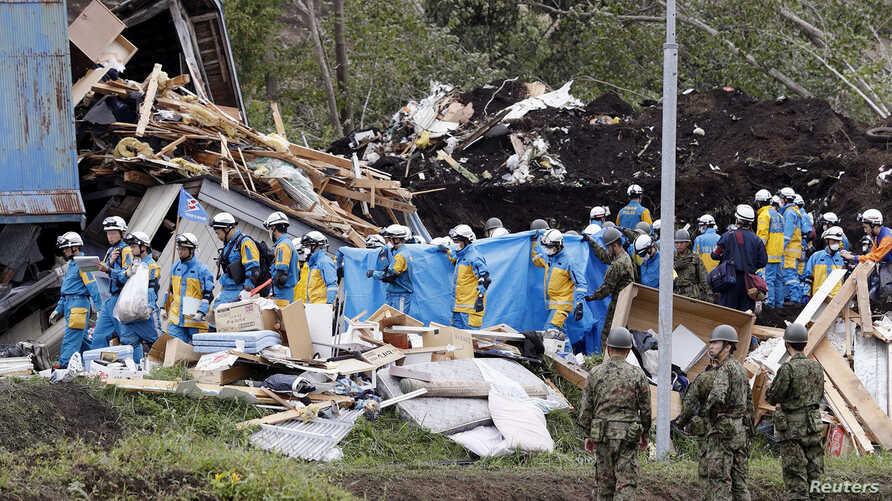 Police officers and members of the Japan Self-Defense Forces (JSDF) carry a missing person found from an area damaged by a landslide caused by an earthquake in Atsuma town, Hokkaido, northern Japan, in this photo taken by Kyodo, Sept. 8, 2018.