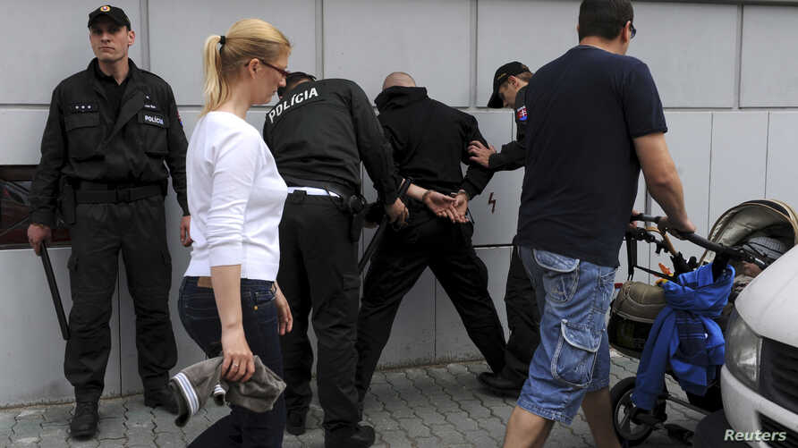 FILE - Policemen detain a member of a Slovak far-right radical organization during a rally in Bratislava, Slovakia, May 22, 2010.