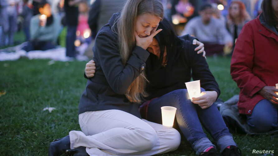 Sisters Heidi Wickersham, left, and Gwendoline Wickersham join in a candlelight vigil Saturday for those killed two days earlier at Umpqua Community College, near Roseburg, Ore. The gunman killed nine people before commiting suicide, Oct. 1, 2015..