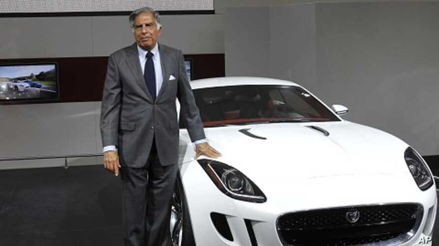 Chairman of Tata Group Ratan Tata poses with Jaguar's newly launched C-X16 car during India's Auto Expo, in New Delhi January 5, 2012.
