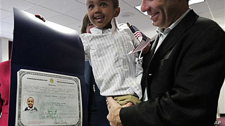 Aaron Lieberman holds his son Theodore, 2, adopted from Ethiopia, as he shows his citizenship certificate, during U.S. Citizenship and Immigration Services (USCIS) Adoption Day ceremony in New York, 18 Nov 2010