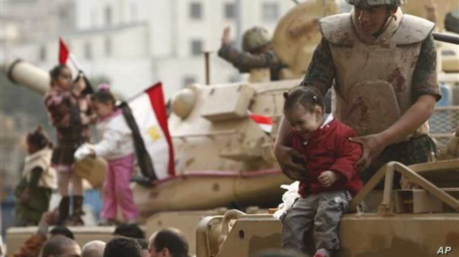 A soldier holds a crying girl from his armored vehicle just outside Tahrir Square in Cairo, Egypt, Feb 1, 2011