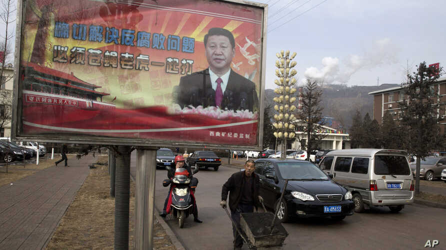 """FILE - A billboard shows Chinese President Xi Jinping with the slogan """"To exactly solve the problem of corruption, we must hit both flies and tigers"""" in Gujiao in northern China's Shanxi province."""