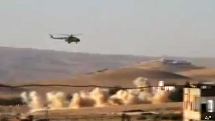 This citizen journalism image provided by Shaam News Network purports to show a helicopter gunship flying a bombing run in al-Qalmoun, Syria, July 24, 2012.