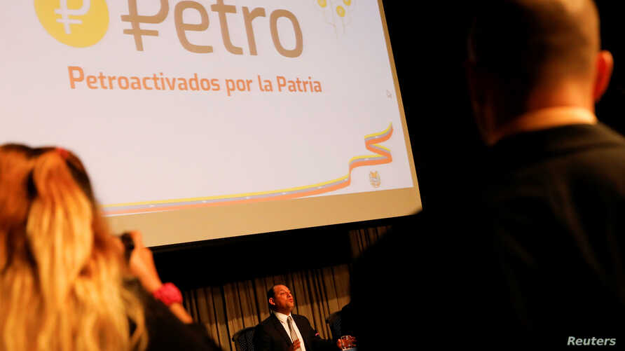 FILE - The new Venezuelan cryptocurrency the Petro logo is seen as Minister for University Education, Science and Technology Hugbel Roa talks to the media during a news conference in Caracas, Venezuela, Jan. 31, 2018.