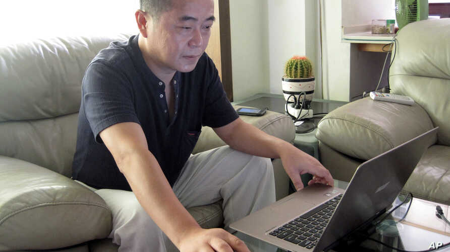 FILE -Veteran rights activist Huang Qi works on his laptop in his home in Chengdu in southwestern China's Sichuan province, Sept. 18, 2012.