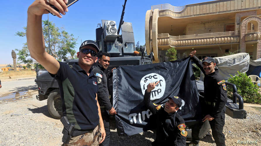 Members of the Iraqi Army are photographed with an Islamic State flag, claimed after fighting with Islamic State militants in western Mosul, Iraq June 26, 2017.