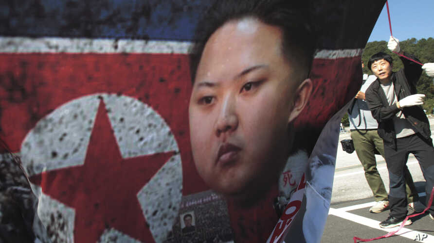 FILE - North Korean defector Park Sang Hak, right, carries a poster showing North Korean leader Kim Jong-Un during an anti-North Korea rally near the Unification Observation Post in Paju, South Korea