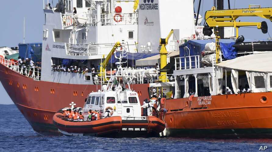 """An Italian Coast Guard boat approaches the French NGO """"SOS Mediterranee"""" Aquarius ship as migrants are being transferred, in the Mediterranean Sea, June 12, 2018."""