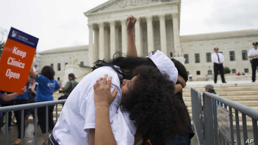Jackelin Alfaro, 7, of Washington hugs her aunt Gelin Alfaro, of Veracruz, Mexico, during an immigration rally at the Supreme Court in Washington, June 23, 2016.