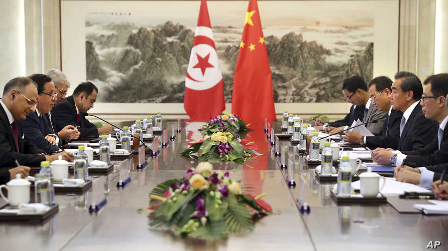 China's Foreign Minister Wang Yi, second from right, speaks as Tunisia's Foreign Minister Khemaies Jhinaoui, second from left, listens during a meeting at the Ministry of Foreign Affairs in Beijing, July 19, 2017.
