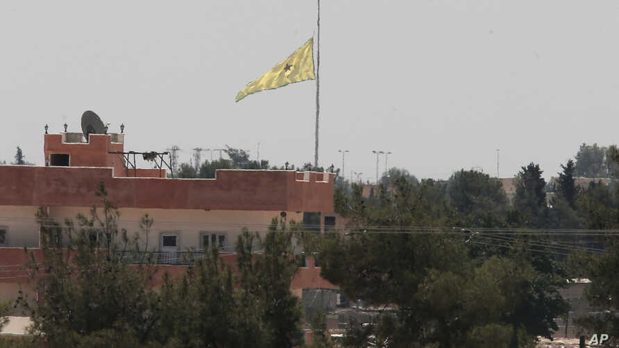 In this photo taken from the Turkish side of the border between Turkey and Syria, in Akcakale, southeastern Turkey, a flag of the Kurdish People's Protection Units, or YPG, flies over the town of Tal Abyad, Syria, June 16, 2015.
