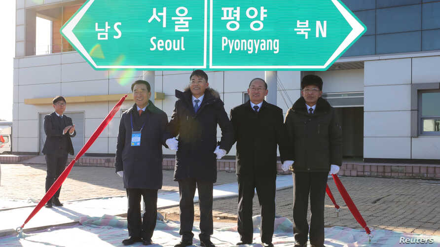 South and North Korean officials unveil the sign of Seoul to Pyeongyang during a groundbreaking ceremony for the reconnection of railways and roads at the Panmun Station in Kaesong, North Korea, Dec. 26, 2018.  (Yonhap via Reuters)