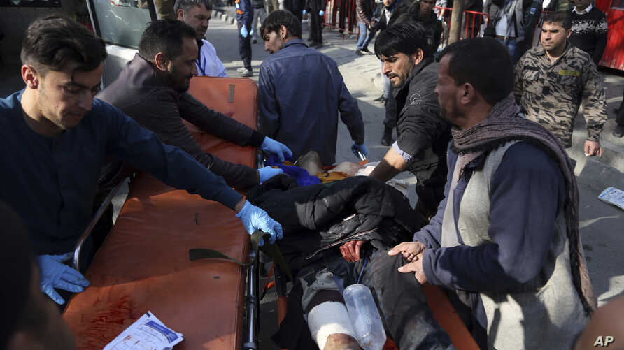 An injured man is moved to a stretcher outside a hospital following a suicide attack in Kabul, Afghanistan, Jan. 27, 2018.