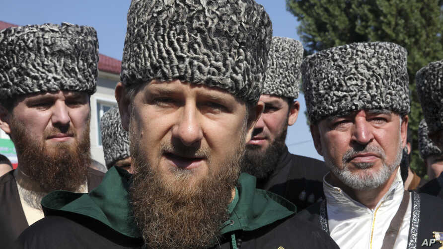 Chechen regional leader Ramzan Kadyrov, center, talks to the media, outside a polling station during parliamentary elections in Chechen town of Tzentoroi, Russia, Sept. 18, 2016.