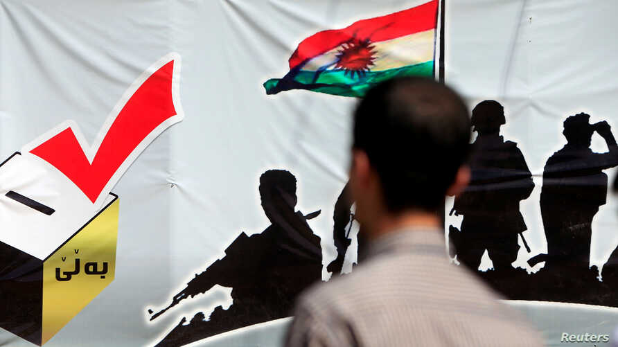 A man looks at a banner supporting the referendum for independence of Kurdistan in Erbil, Iraq, Sept. 24, 2017.