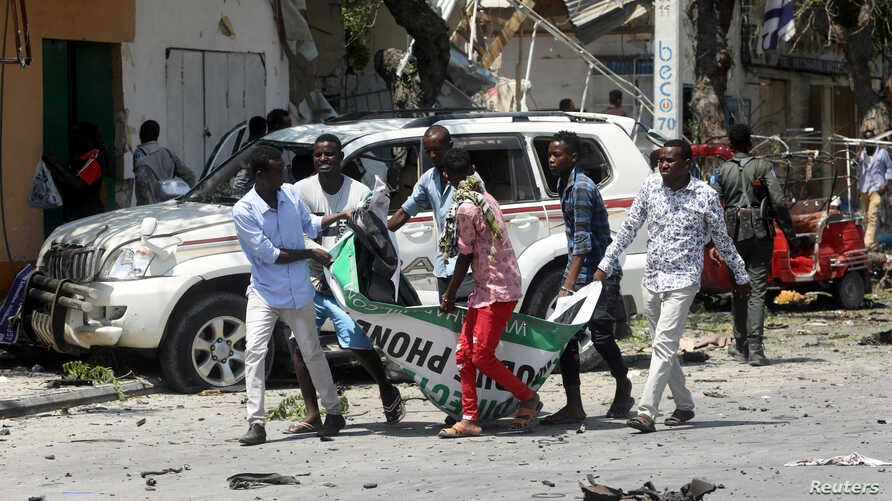 Civilians carry the dead body of a man killed in a car bomb explosion near a hotel in Mogadishu, Somalia, March 28, 2019.