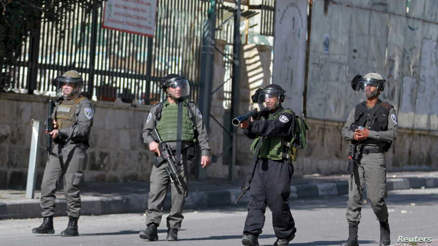 FILE - An Israeli border policeman aims his weapon towards Palestinian protesters as others take up position during clashes in the West Bank city of Bethlehem, Jan.  22, 2016.