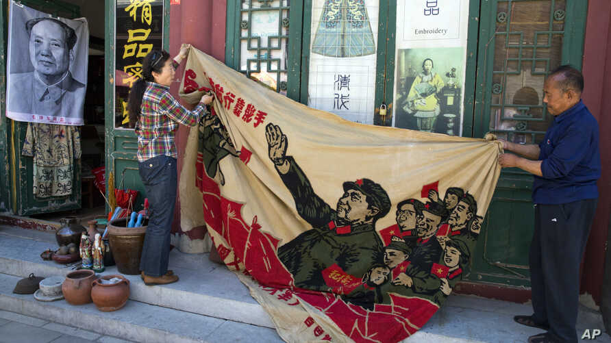 "Vendors unfurl a banner from 1969 depicting former Chinese leader Mao Zedong as he ""inspects the great army of the Cultural Revolution"" and the slogan ""Navigating the seas depends on the helmsman"" at a curio market in Beijing, China, May 16, 2016."
