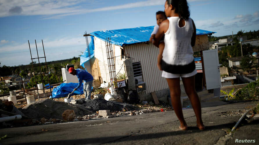 Samuel Vasquez rebuilds his house, which was partially destroyed by Hurricane Maria, while his wife Ysamar Figueroa looks on, whilst carrying their son Saniel, at the squatter community of Villa Hugo in Canovanas, Puerto Rico, Dec. 11, 2017. Villa Hu