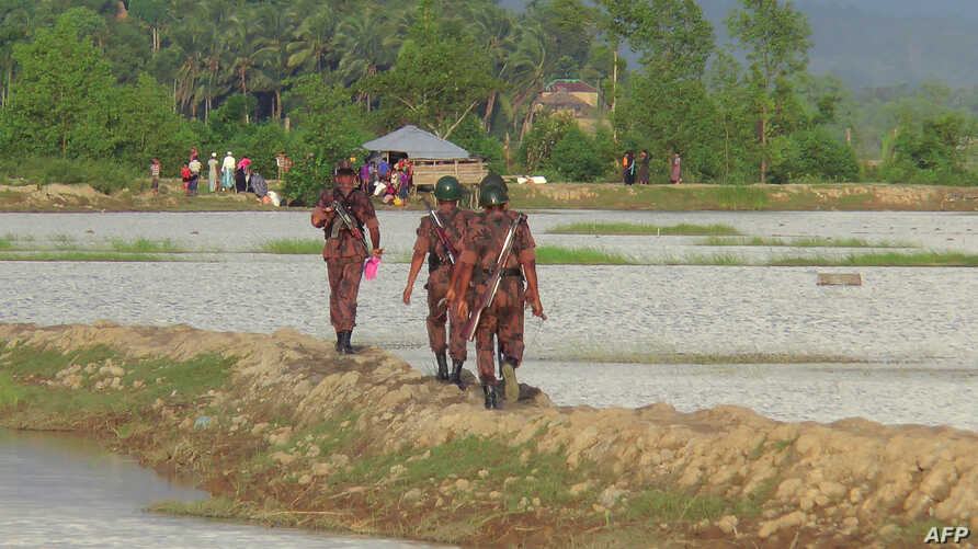 Rohingya people (back) from Rakhine state in Myanmar gather near the border in Ukhiya town, where Bangladeshi border guards were stopping them from entering, on August 25, 2017.