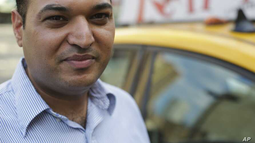 In this July 21, 2015 photo, yellow cab driver Jatinder Singh poses for a portrait near his taxi in New York.