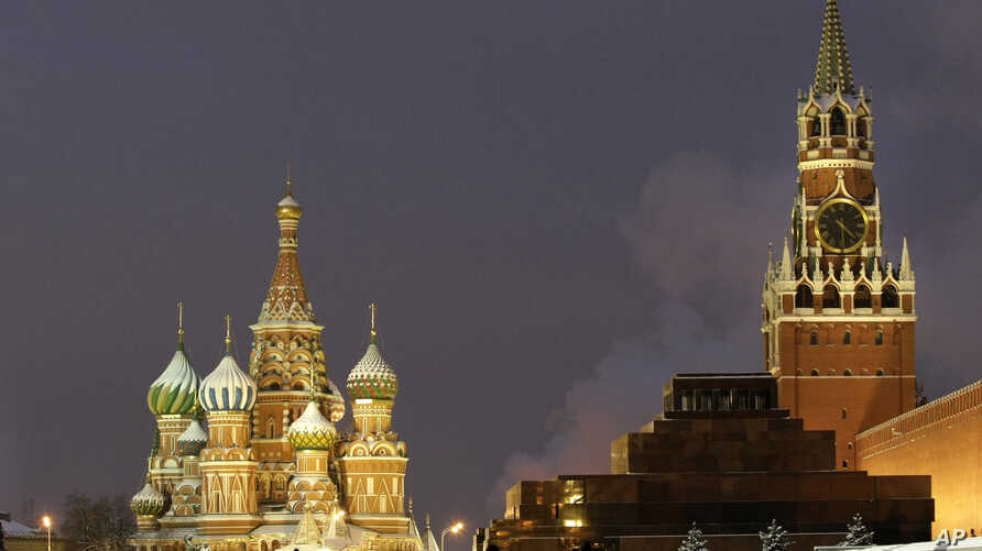 FILE - People walk in Red Square, with St. Basil Cathedral (left) the Kremlin's Spassky Tower (right rear) and Lenin Mausoleum (right) in Moscow, Dec. 10, 2009.