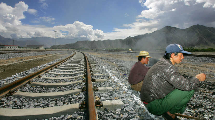 FILE - Workers take a break sitting on the tracks leading to the platform of the newly opened Lhasa train station in Lhasa, Tibet, China.