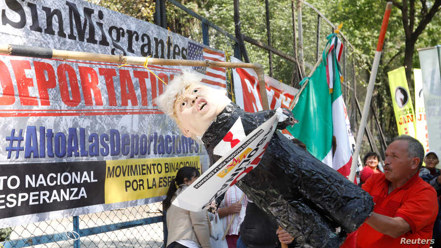 An activist hits a pinata resembling U.S. President Donald Trump as they mark the one-year anniversary of Trump's inauguration with a protest outside the U.S. embassy in Mexico City, Mexico, Jan. 20, 2018.