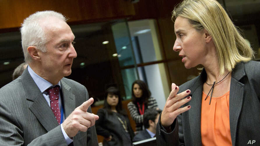 EU Counter-Terrorism chief Gilles de Kerkhove, left, gestures while speaking with European Union High Representative Federica Mogherini during a meeting of EU foreign ministers in Brussels, Jan. 19, 2015.